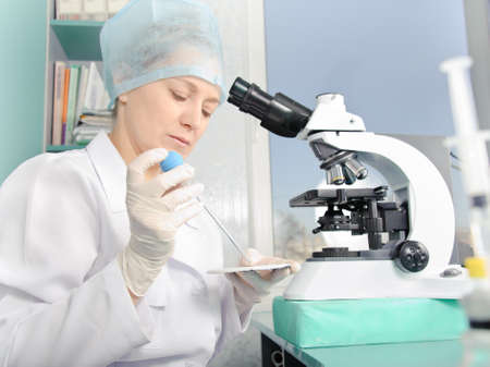 eyepiece: Female scientist working at the laboratory. White uniform and gloves. Focus on the face and hands.