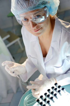 forensics: Female doctor in glasses examines a sample.  Could be useful for medicine, hospital, research and development, clinical studies, forensics, science etc