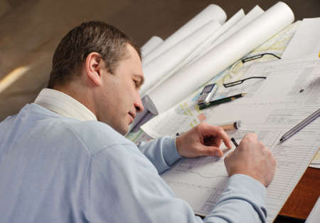 architect drawing: Architect or constructor in blue pullover is working on construction plans
