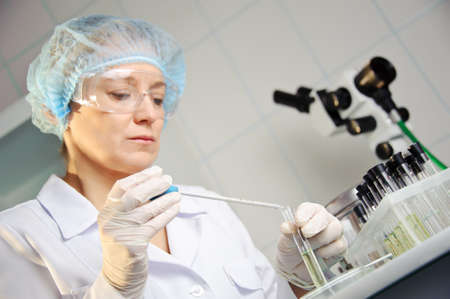 A female doctor examines a sample. Shallow depth of field. Focus on foreground, hands. Could be useful for medicine, hospital, research and development, clinical studies, forensics, science etc photo