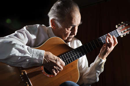 70 80: An elderly man in white shirt playing an acoustic guitar  Dark background