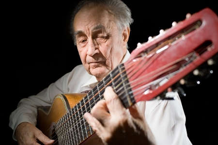 10 fingers: An elderly man in white shirt playing an acoustic guitar  Dark background