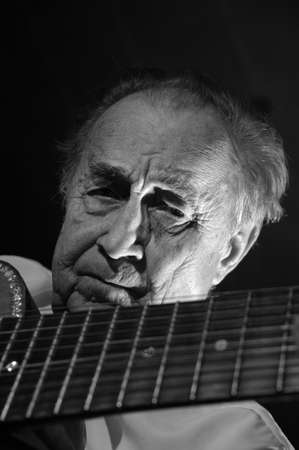 An elderly man in white shirt playing an acoustic guitar. Dark background. Monochrome. photo