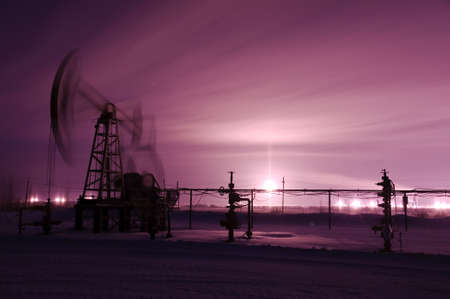 jack pump: Oil and gas industry. Pump jack. Monochrome. Winter night view. Stock Photo