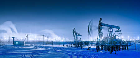 drilling rig: Oil and gas industry. Panoramic of a pumpjack and oil refinery in the winter with snow. Night view.