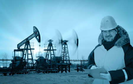 Oil worker in orange uniform and helmet on of background the pump jacks and sunset sky. Monochrome.