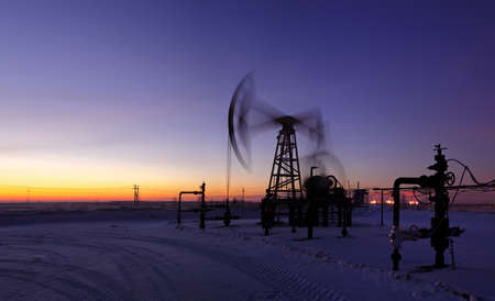 Pumpjack on the sunset sky background. Long exposure. Panorama. photo