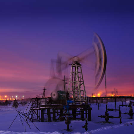 Oil pump-jack in action. Night view. Long exposure. photo