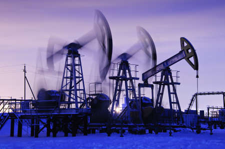 oil pumps at sunset sky background. blue toned.
