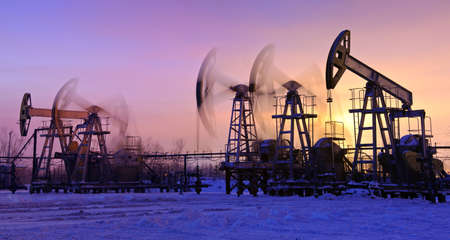 oil field: oil pumps at sunset sky background. panorama.
