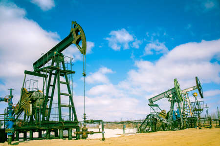Oil and gas industry. Pump jack on a sky background. Toned. Archivio Fotografico