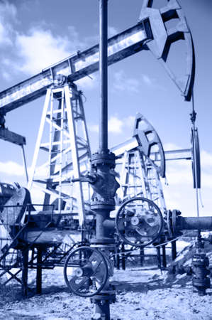 Wellhead with valve armature and pump jack  Extraction of oil  Toned  photo