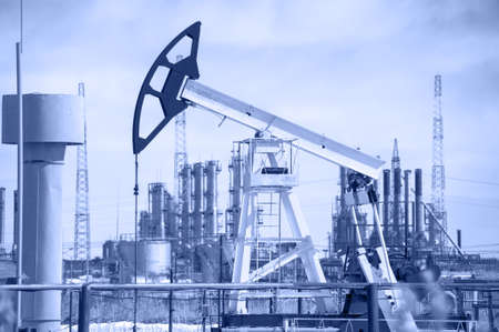 oil well: Pump jack on a background of petrochemical plant  Oil and gas industry  Toned  Stock Photo