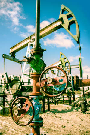 Extraction of oil  Wellhead with valve armature and pump jack  Toned  photo