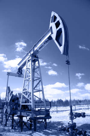 Pump jack and wellhead with valve armature  Extraction of oil  Toned  photo