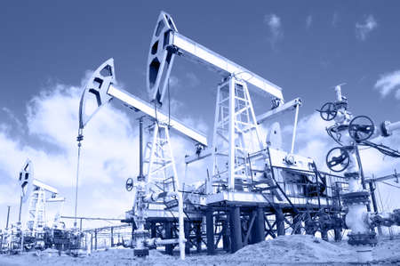Pump jack and wellhead with valve armature  Extraction of oil  Stock Photo