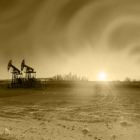 oil and gas industry: Oil pumps on the sunset sky background. Toned sepia. Stock Photo