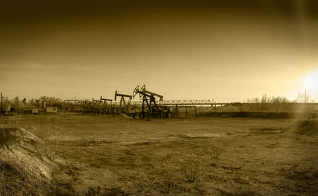 oilwell: Pump jack group and wellheads. Extraction of oil. Toned.