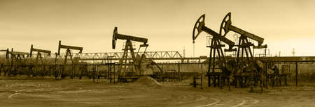 oil and gas: Pump jack group and wellheads. Extraction of oil. Toned.