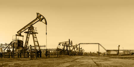 industrial machinery: Pump jack group and wellheads. Extraction of oil. Toned.
