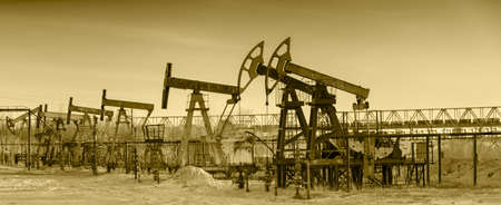 pump jack: Pump jack group and wellheads. Extraction of oil. Toned.