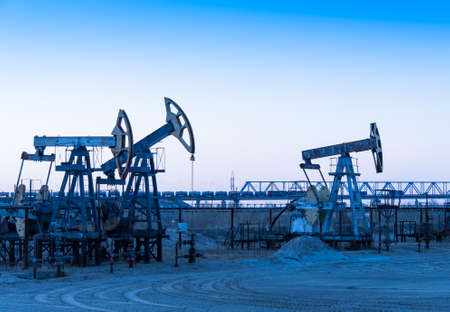 jack pump: Pump jack group on a sunset sky background. Extraction of oil. Toned. Stock Photo