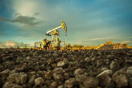 mineria: conectores de la bomba de aceite en el fondo del cielo puesta del sol.