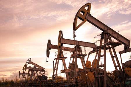 jacks: Oil pump jacks at sunset sky background. Toned.