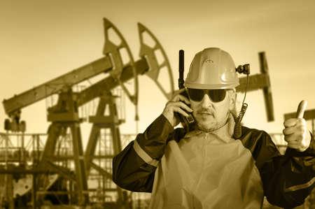 trabajador petrolero: Trabajador adulto industrial en gafas, con cámara de casco, hablando por transceptor de radio, en un fondo del campo de petróleo. Tonos sepia.