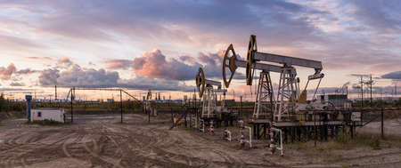 Oil and gas industry. Panoramic of a pumpjack and oil refinery.
