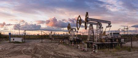 huile: L'industrie pétrolière et gazière. Panoramique d'un chevalet de pompage et de la raffinerie de pétrole.