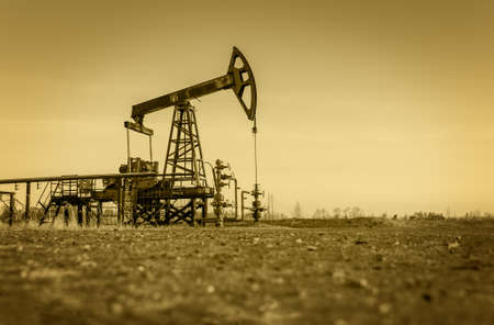 pump jack: Pump jack and wellheads. Extraction of oil. Toned.