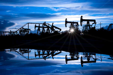 jack pump: Oil pump jacks group on a sunset sky background. Toned blue. Stock Photo