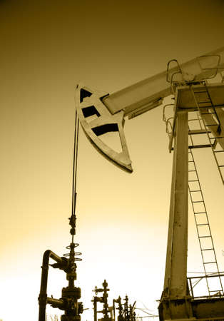 pump jack: Pump jack and wellheads. Extraction of oil. Toned sepia. Stock Photo