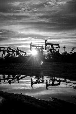 jacks: Oil pump jacks at sunset sky background. Black and white.
