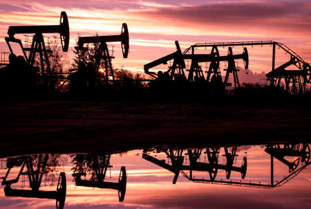 jacks: Oil pump jacks at sunset sky background. Toned.