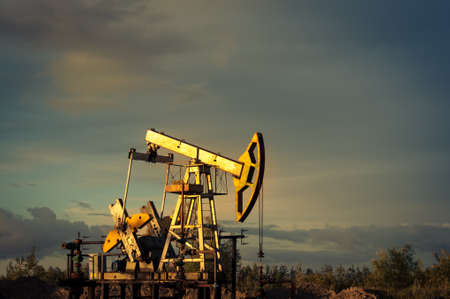 oil and gas: Oil pump jacks at sunset sky background.