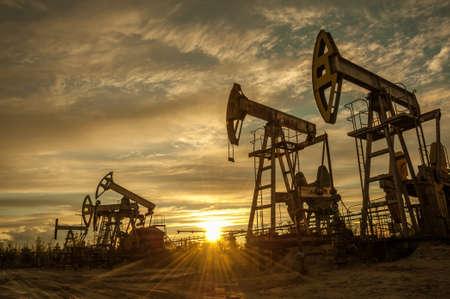 Oil pump jacks at sunset sky background. Toned.