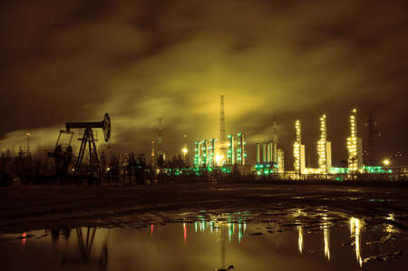 oil well: Oil rigs and brightly lit industrial site at night. Toned. Stock Photo