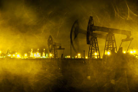 Group oil rigs and brightly lit industrial site at night. Raindrops texture. Through wet glass. Toned golden.