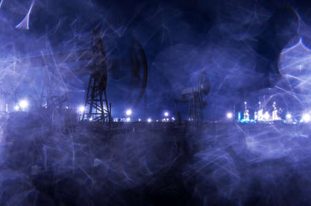 torres petroleras: Plataformas petroleras del Grupo y sitio industrial brillantemente iluminado en la noche. Las gotas de lluvia textura. A través de un vidrio mojado. Virada azul. Foto de archivo