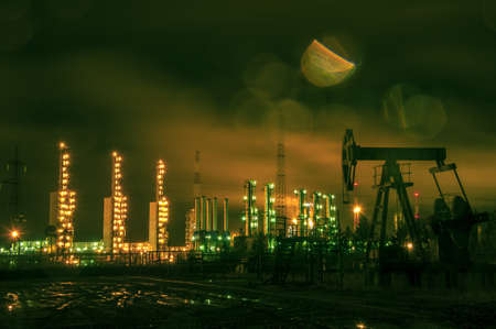 torres petroleras: Oil rigs and brightly lit industrial site at night. Toned. Foto de archivo