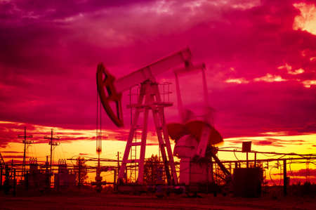 oil field: Oil pump jacks at sunset sky background. Oil and gas industry. Blurred motion. Toned.