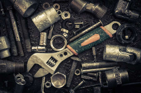 metal working: Grunge background with wet tools and bolts. Adjustable wrench, screws, nuts. Toned. Stock Photo