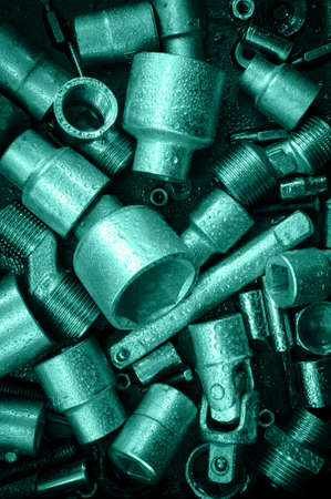 bolts heads: Spanner wrench heads, nuts and bolts on a dark scratched metal background. Toned.