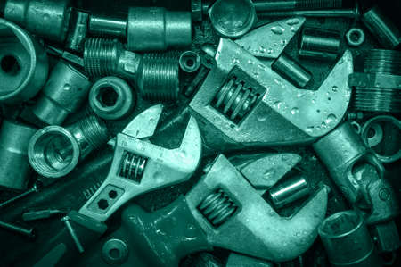 Grange background with wet tools and bolts. Adjustable wrenchs, screws, nuts. Toned.