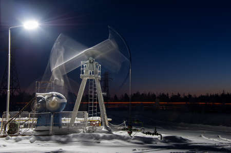 oilwell: Oil pump-jack in action. Night view. Long exposure. Stock Photo