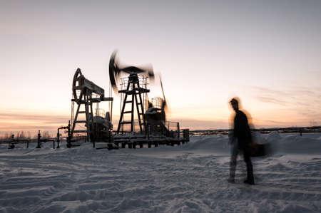 yacimiento petrolero: Los trabajadores del petr�leo en un yacimiento. Gato de la bomba y el ingeniero en un fondo de cielo del atardecer de invierno. Siberia occidental. el movimiento borroso.