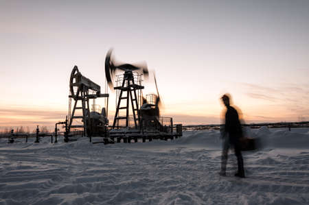 oilfield: Oil worker in a oilfield. Pump jack and engineer on a winter sunset sky background. Western Siberia. Blurred motion.