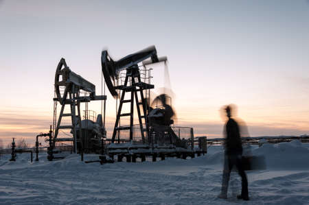 jack pump: Oil worker in a oilfield. Pump jack and engineer on a winter sunset sky background. Western Siberia. Blurred motion.